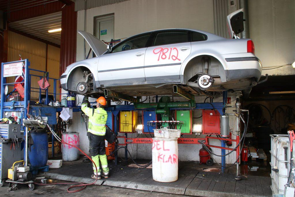 På bildet fjerner og tømmer en av HRS Metallco sine ansatte et kjøretøy for miljøstadelige væsker, som drifstoff, kjøleveske og liknende.